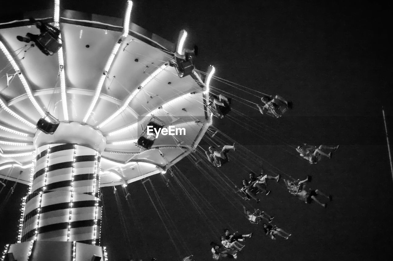 LOW ANGLE VIEW OF ILLUMINATED CAROUSEL