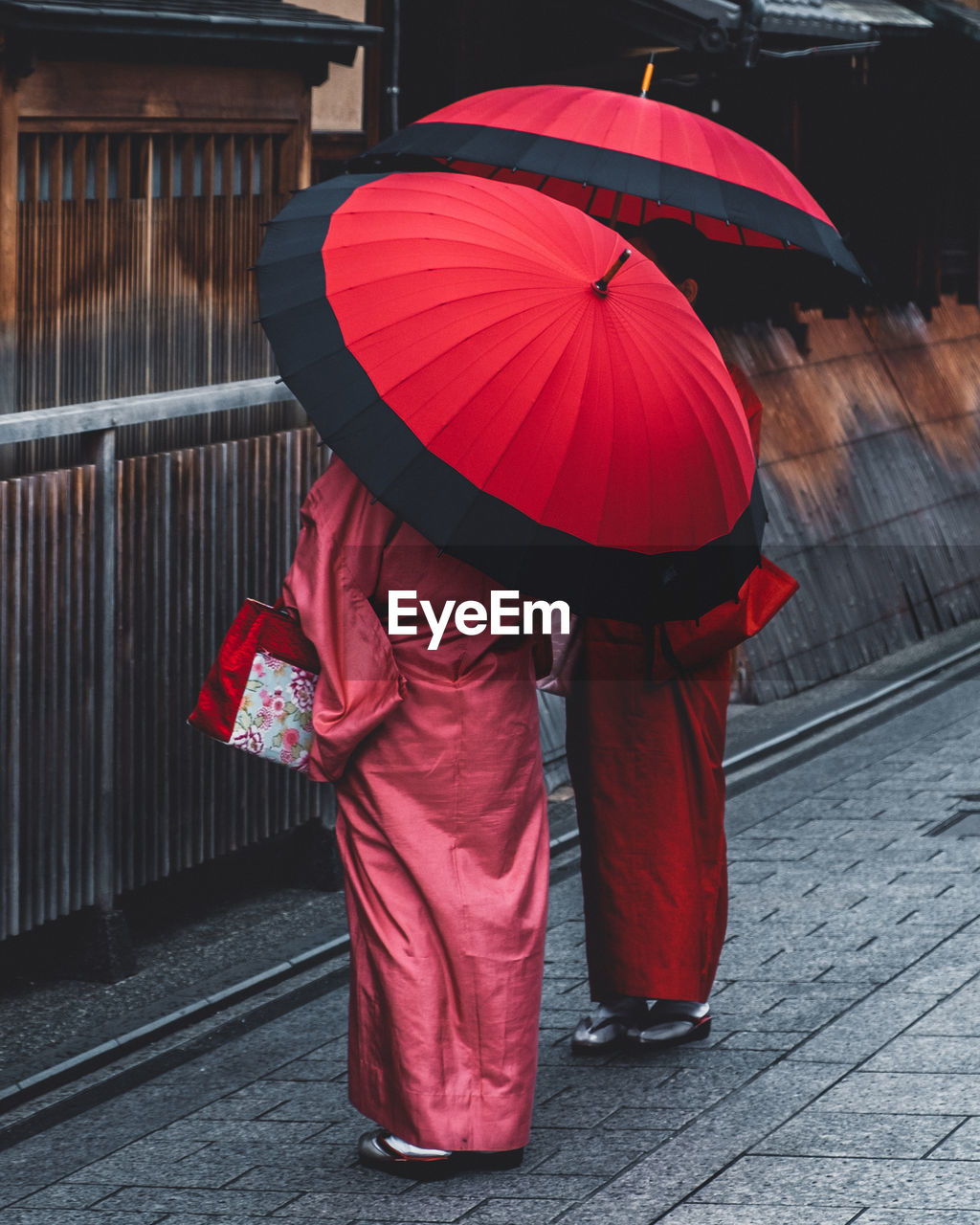 REAR VIEW OF RED WOMAN HOLDING UMBRELLA WALKING ON STREET