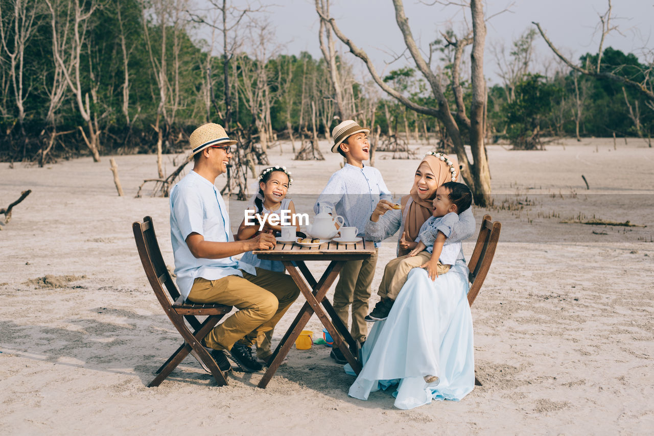 Family Having Breakfast While Sitting On Field