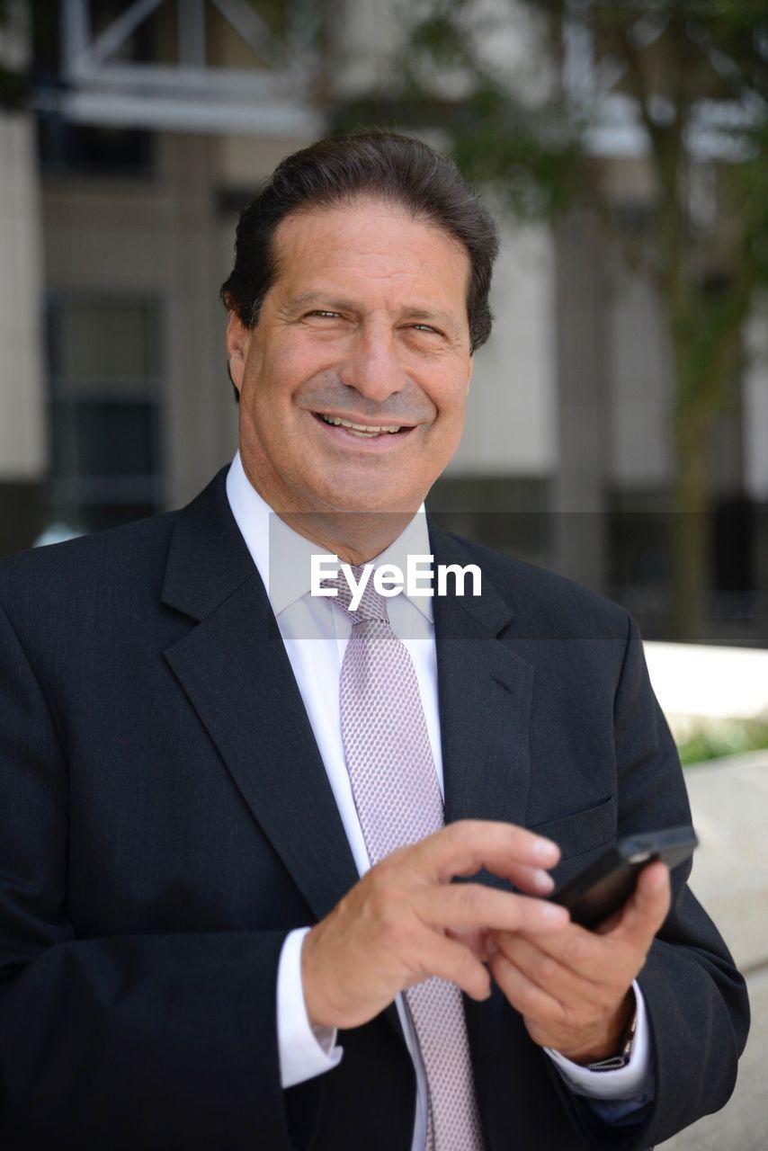 Portrait Of Smiling Man Using Smart Phone
