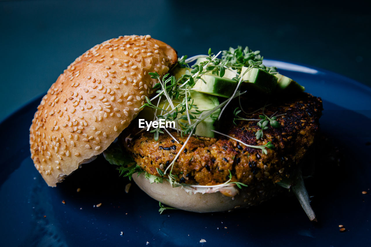 Close-up of fresh veggie burger with avocado and sprouts on plate