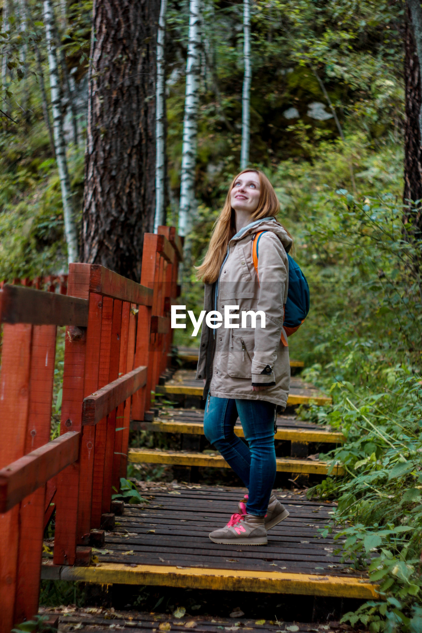 Side view of woman standing on steps in forest