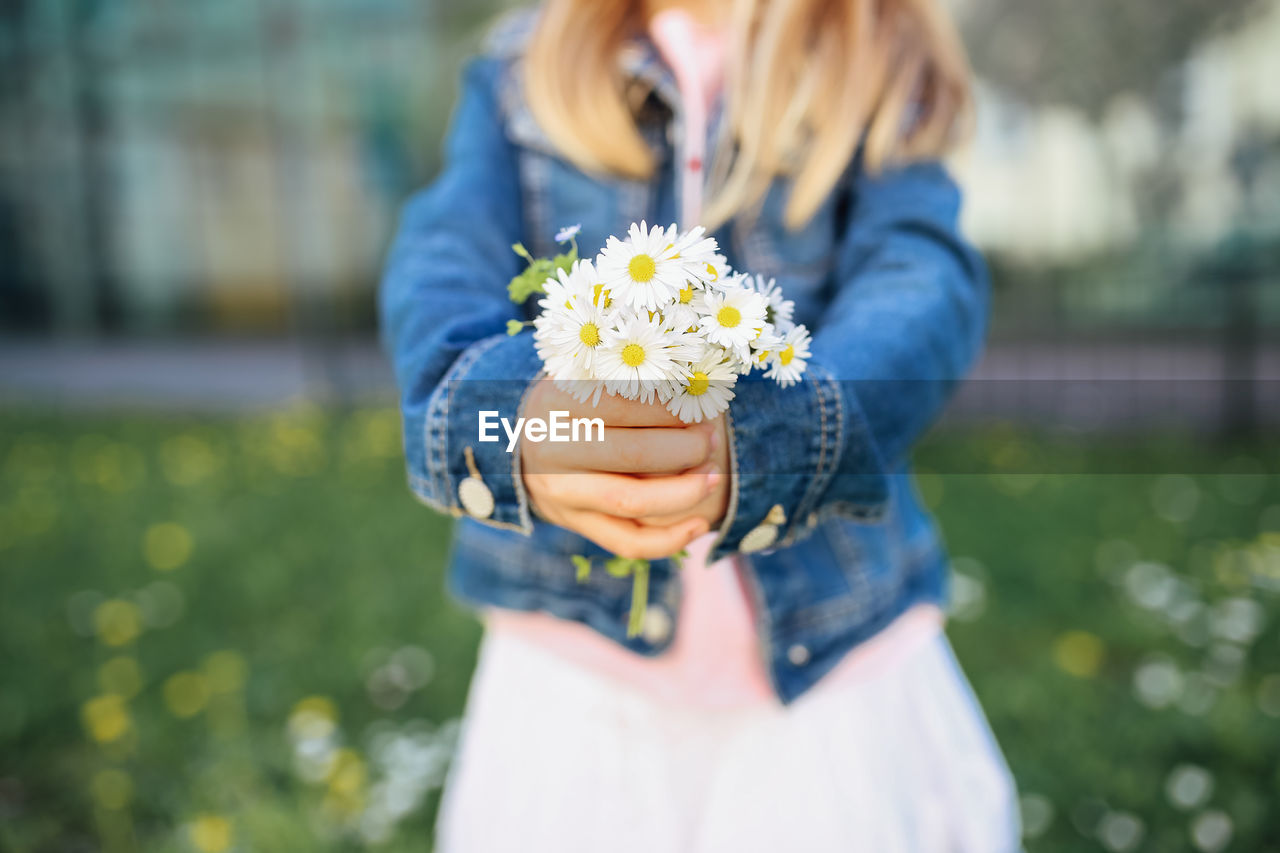 Midsection Of Girl Holding Flowers While Standing On Field