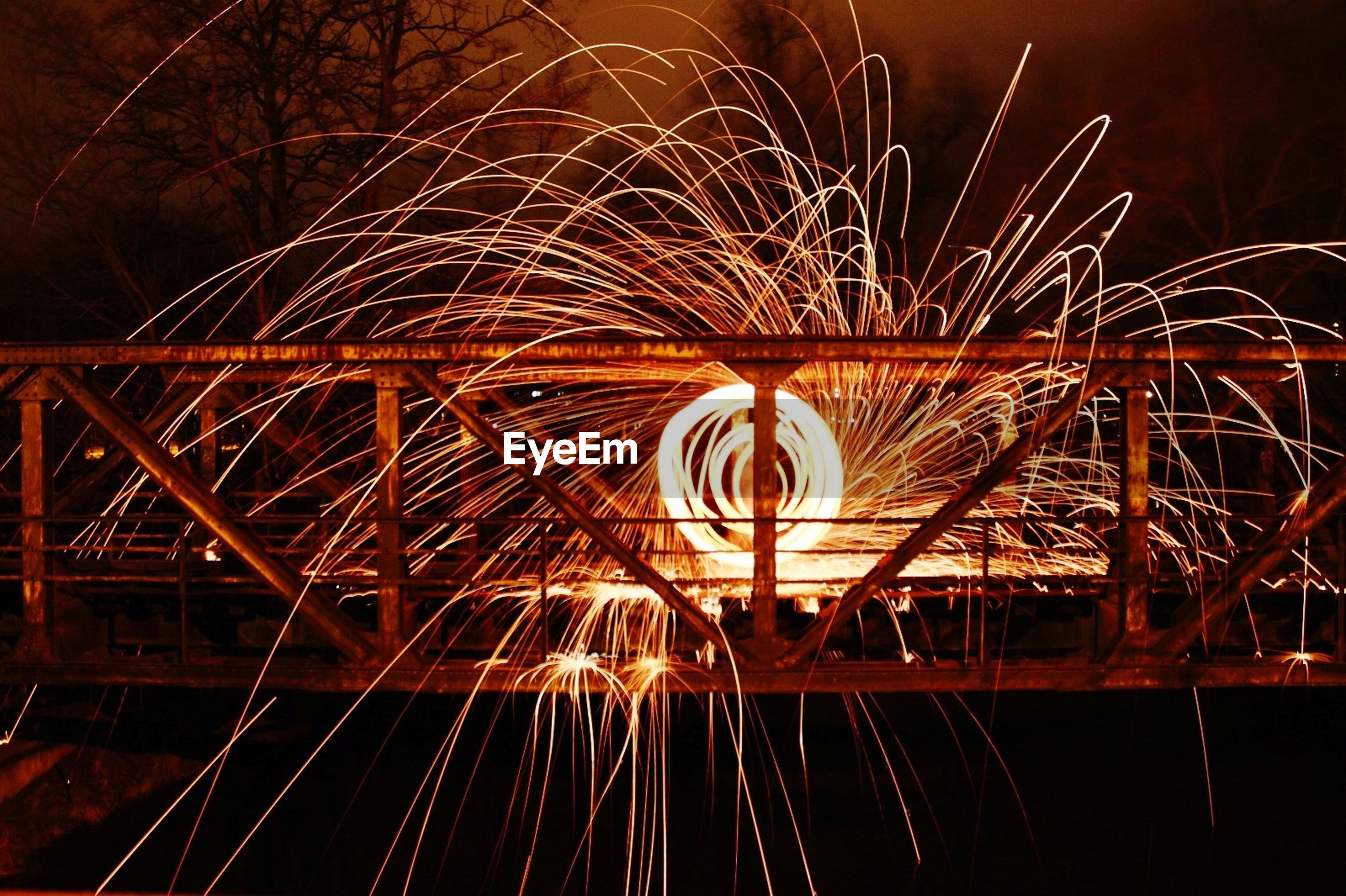 night, illuminated, motion, long exposure, blurred motion, wire wool, glowing, spinning, sparks, nature, arts culture and entertainment, one person, speed, orange color, fire, architecture, burning, outdoors, firework, light, dark, firework display, firework - man made object