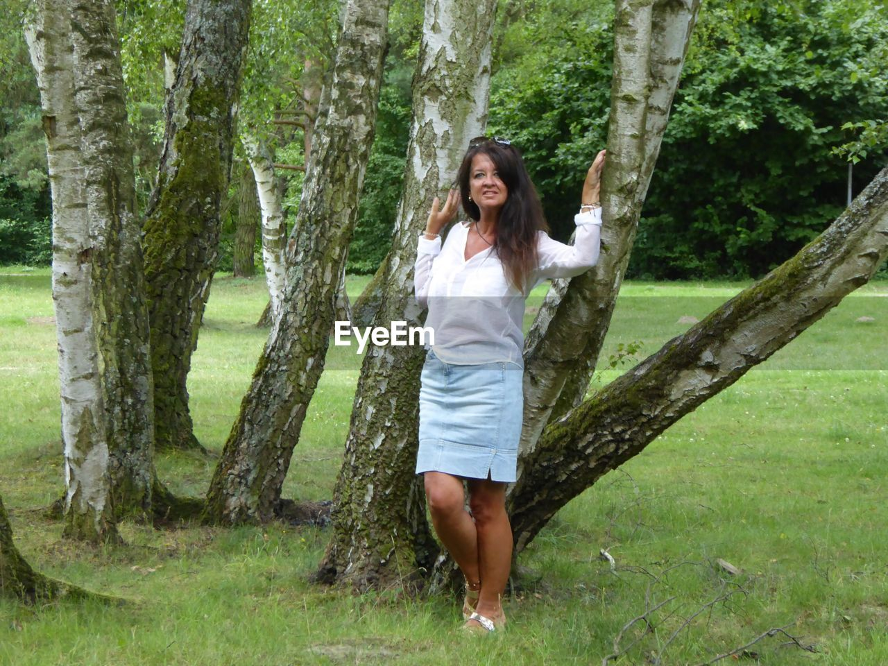 long hair, tree, one person, beautiful woman, young adult, casual clothing, full length, front view, smiling, tree trunk, brown hair, nature, barefoot, happiness, one woman only, adults only, only women, young women, standing, beauty, day, relaxation, portrait, adult, outdoors, looking at camera, leisure activity, real people, cheerful, women, grass, lifestyles, people, one young woman only