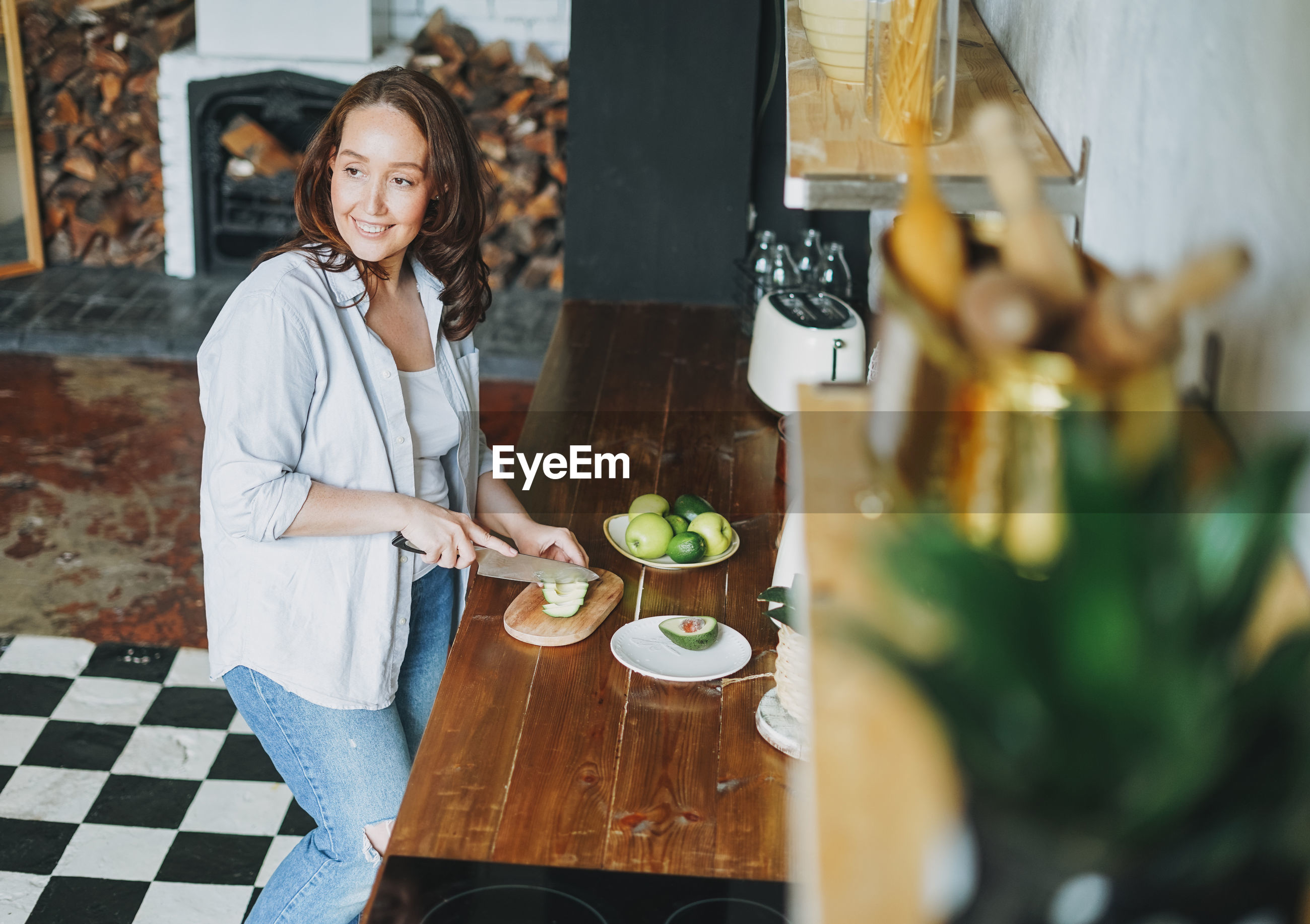 YOUNG WOMAN STANDING BY FOOD ON TABLE