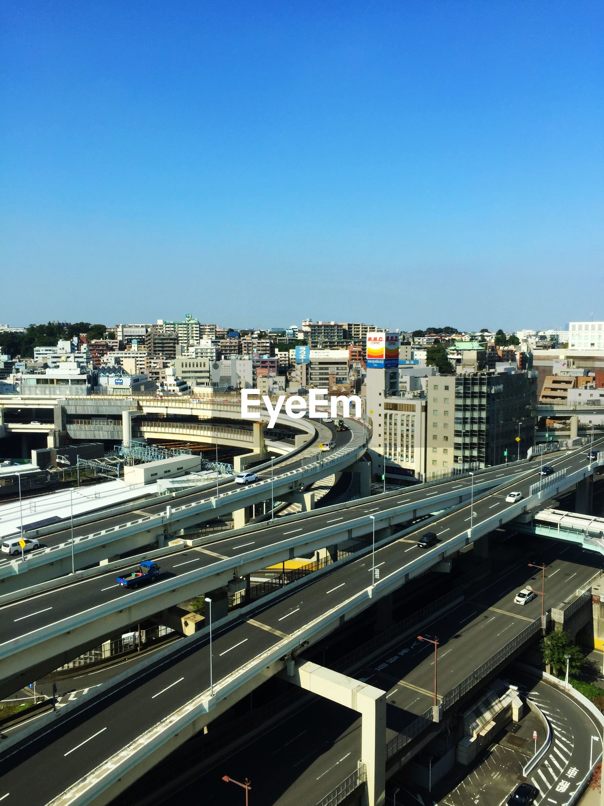 High angle view of highways and buildings in city against clear blue sky