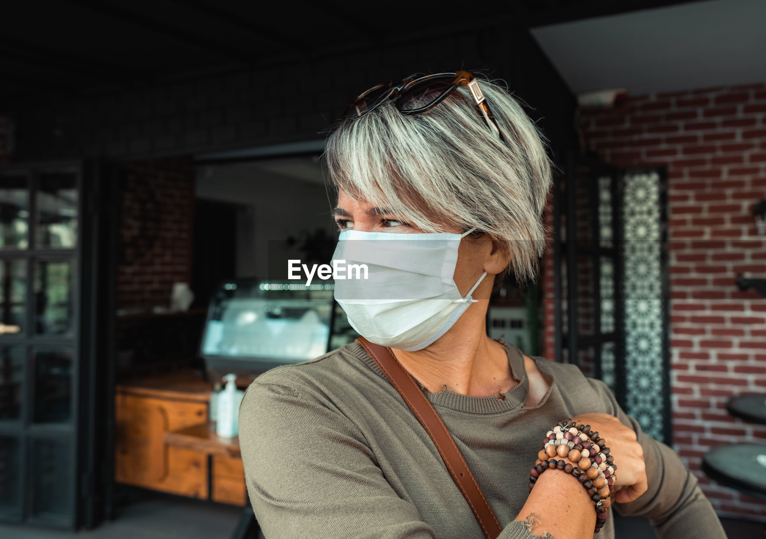 Customer wearing face mask during pandemic time in front of coffee shop.