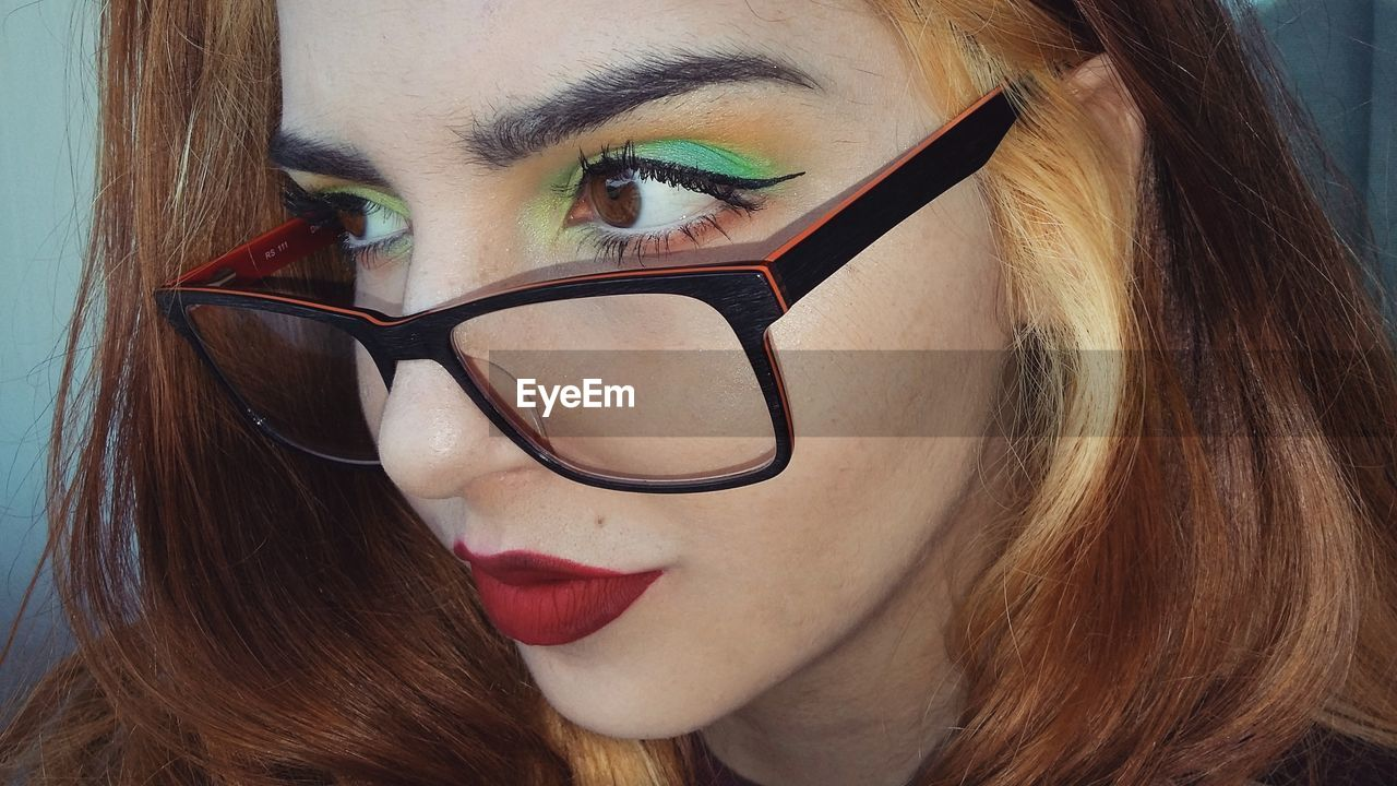 Close-Up Of Thoughtful Young Woman With Make-Up Wearing Eyeglasses