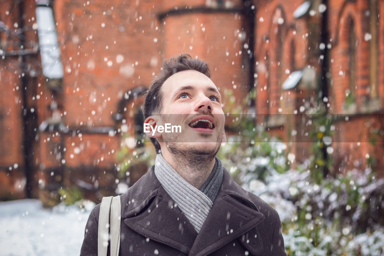 Mid adult man with mouth open looking up during snowfall