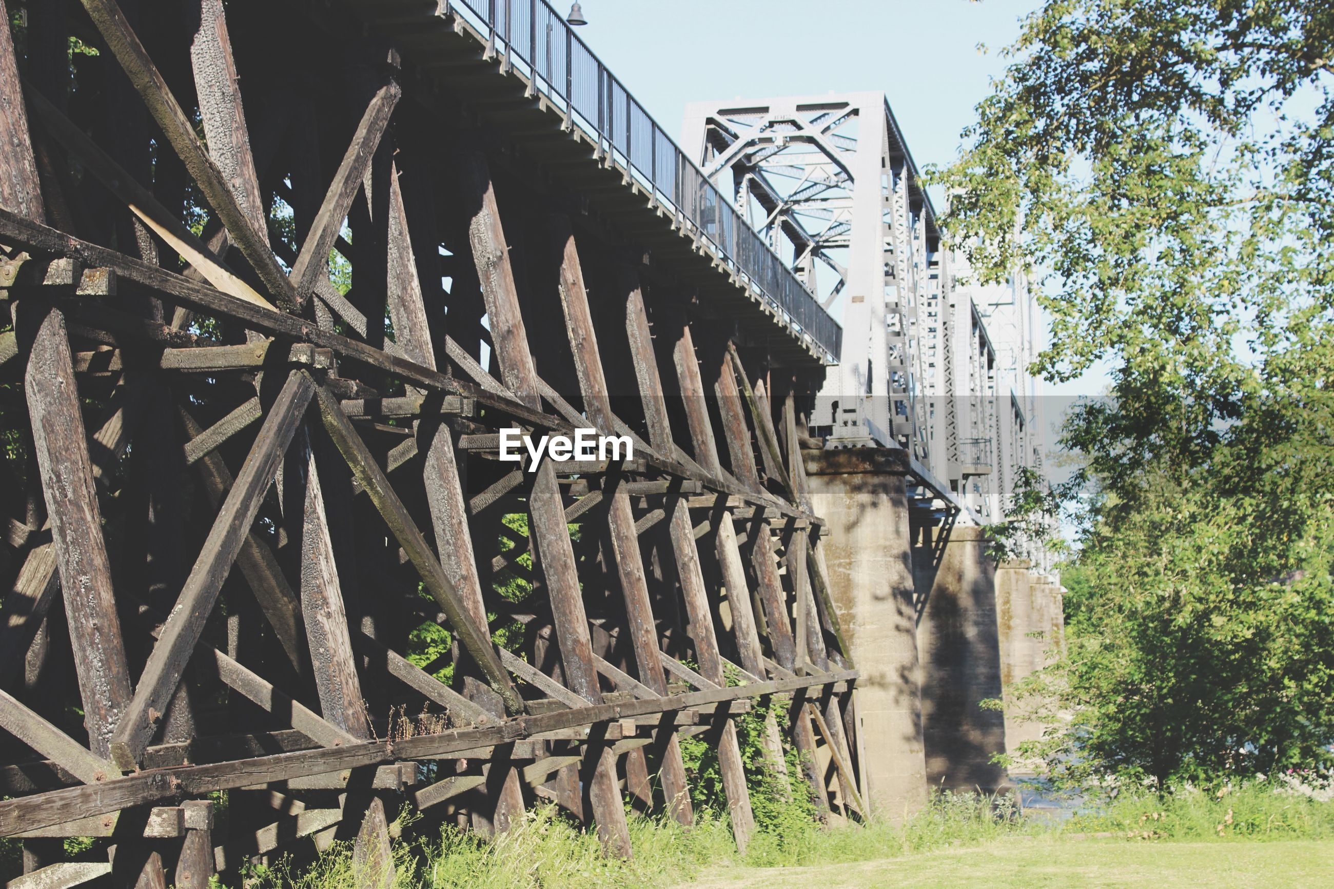built structure, architecture, connection, low angle view, bridge - man made structure, metal, railing, sky, tree, clear sky, old, engineering, day, metallic, no people, outdoors, sunlight, plant, grass, wood - material