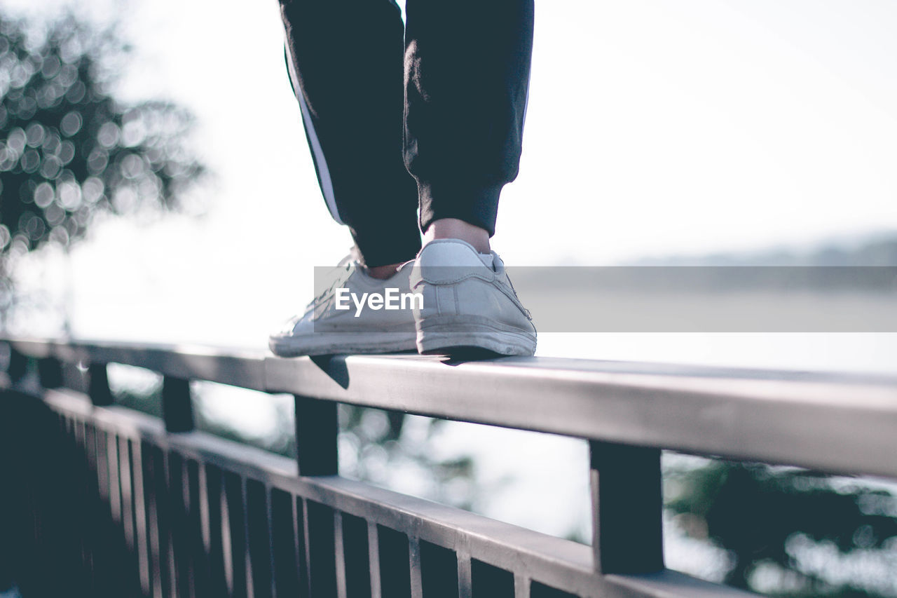 Low Section Of Person Standing On Railing