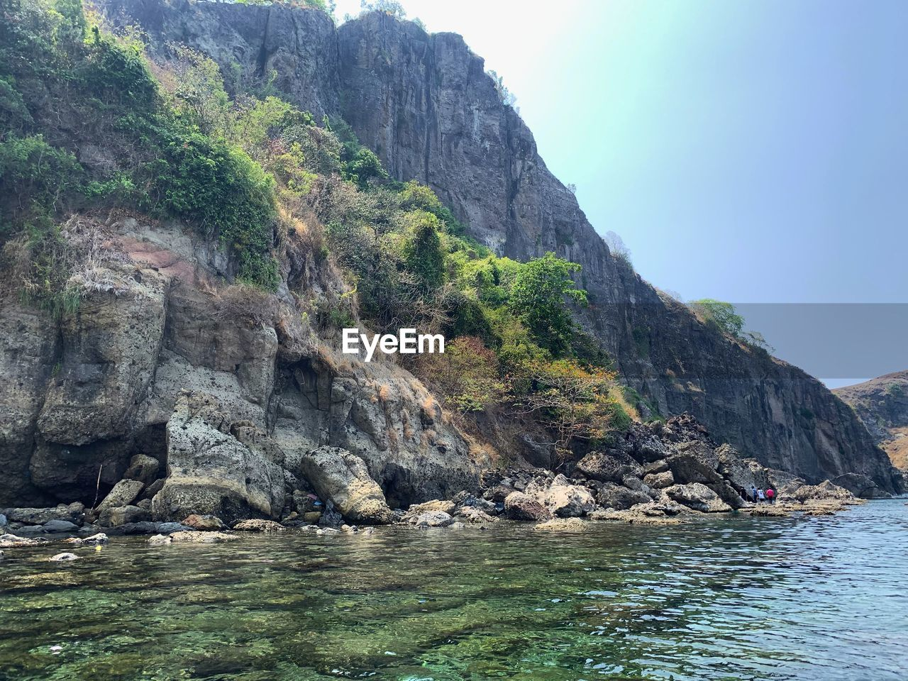 water, rock, mountain, beauty in nature, waterfront, scenics - nature, solid, rock - object, tranquility, nature, sea, rock formation, tranquil scene, sky, day, cliff, idyllic, land, no people, mountain range, outdoors, formation