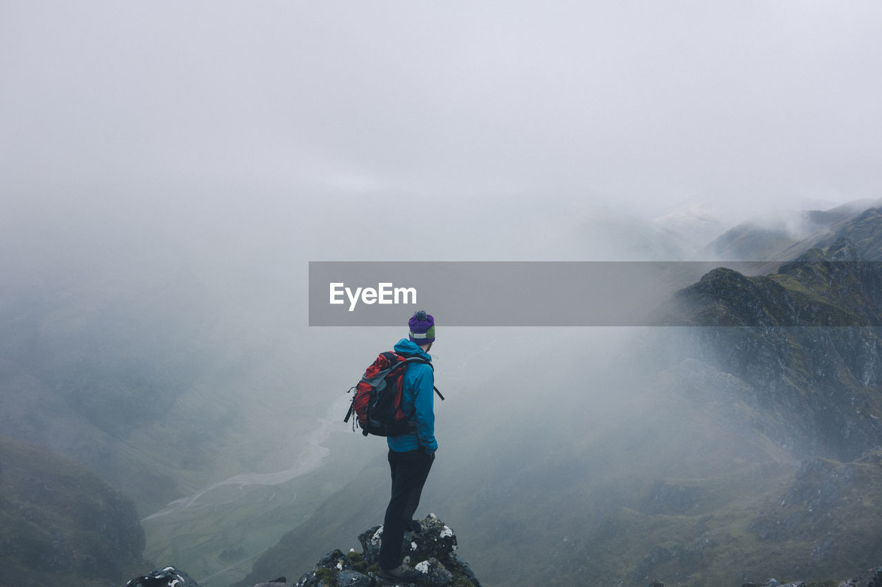 Man Standing On Cliff During Foggy Weather