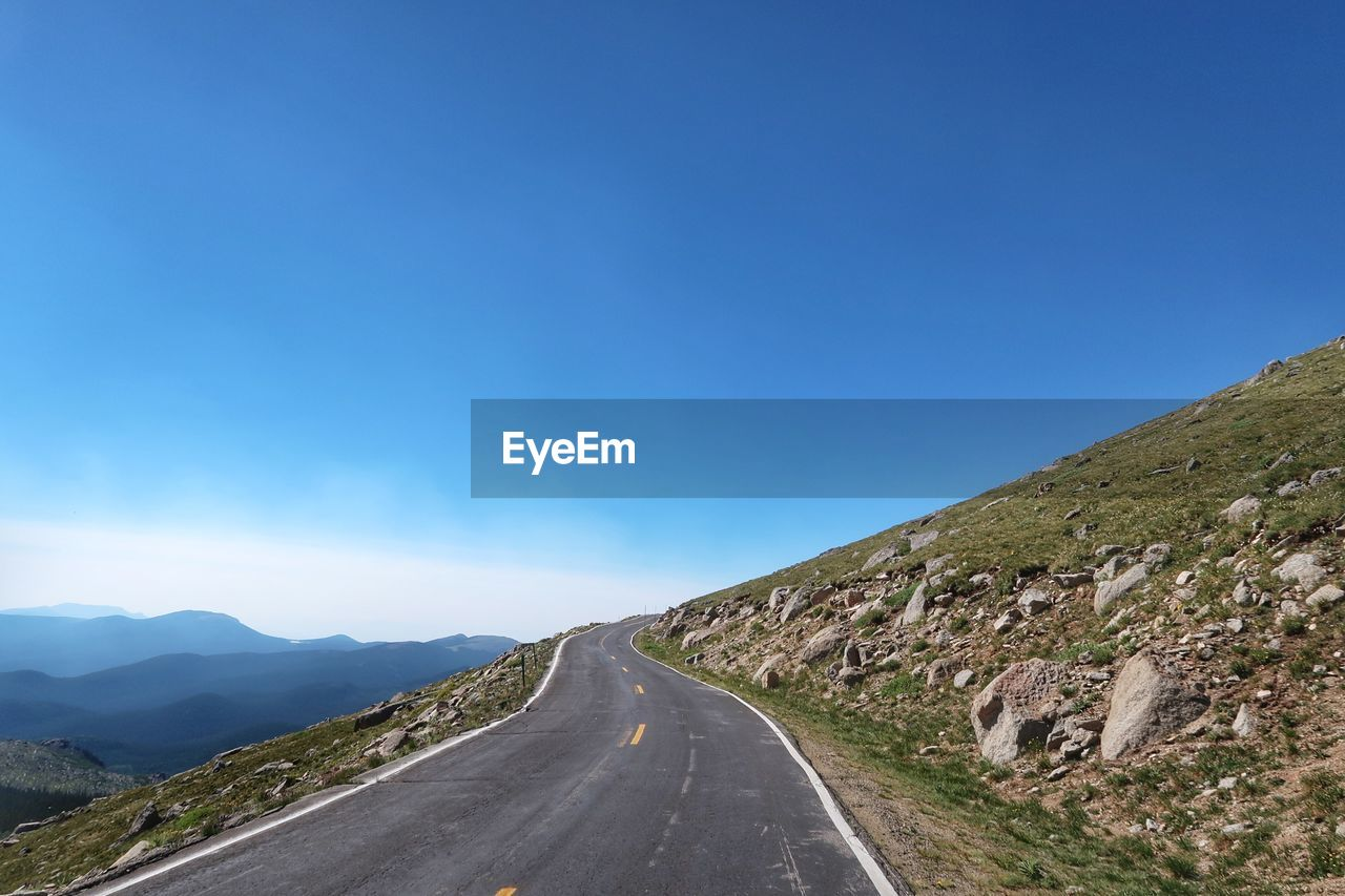 Road Leading Towards Mountains Against Clear Blue Sky