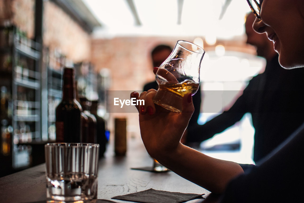 drink, food and drink, refreshment, restaurant, one person, bar - drink establishment, indoors, alcohol, drinking glass, real people, table, holding, drinking, midsection, food and drink industry, cafe, bartender, close-up, men, women, freshness, happy hour, young adult, day, people
