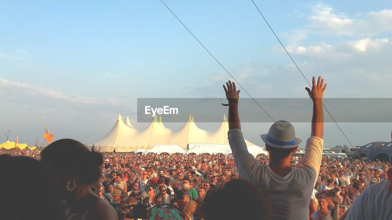 Rear View Of Man Gesturing Crowd Against Sky