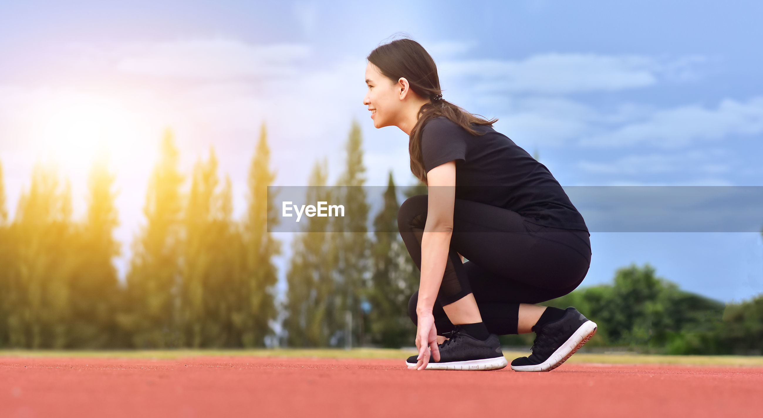 Side view of smiling woman crouching on running track