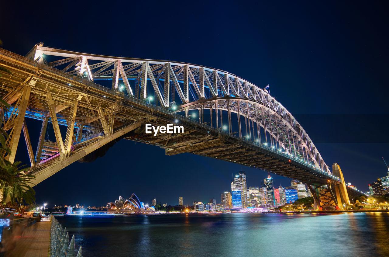 Sydney Harbor Bridge Over Parramatta River Against Sky In City At Night
