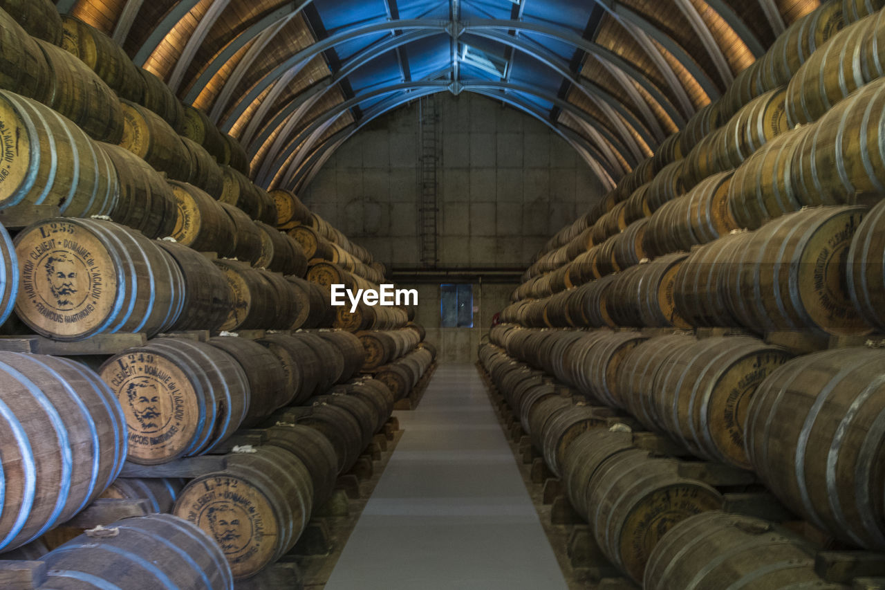 large group of objects, stack, indoors, arrangement, abundance, in a row, food and drink, no people, architecture, order, industry, factory, domestic room, building, metal, barrel, drink, container, refreshment, warehouse, ceiling, winemaking