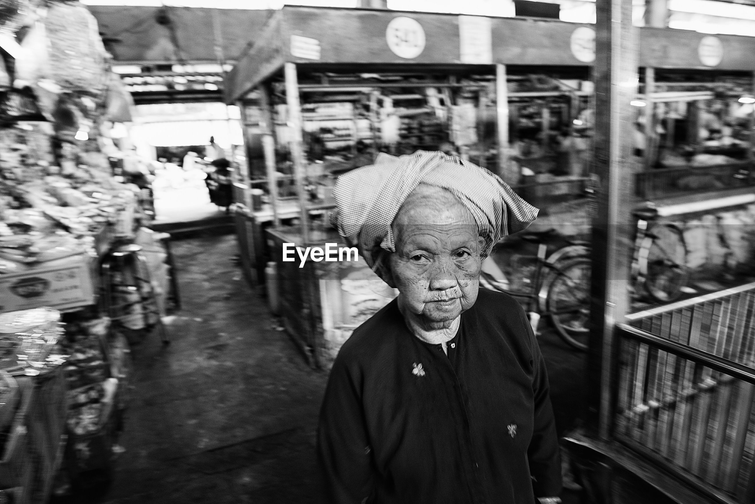 Portrait of senior woman standing at market in city