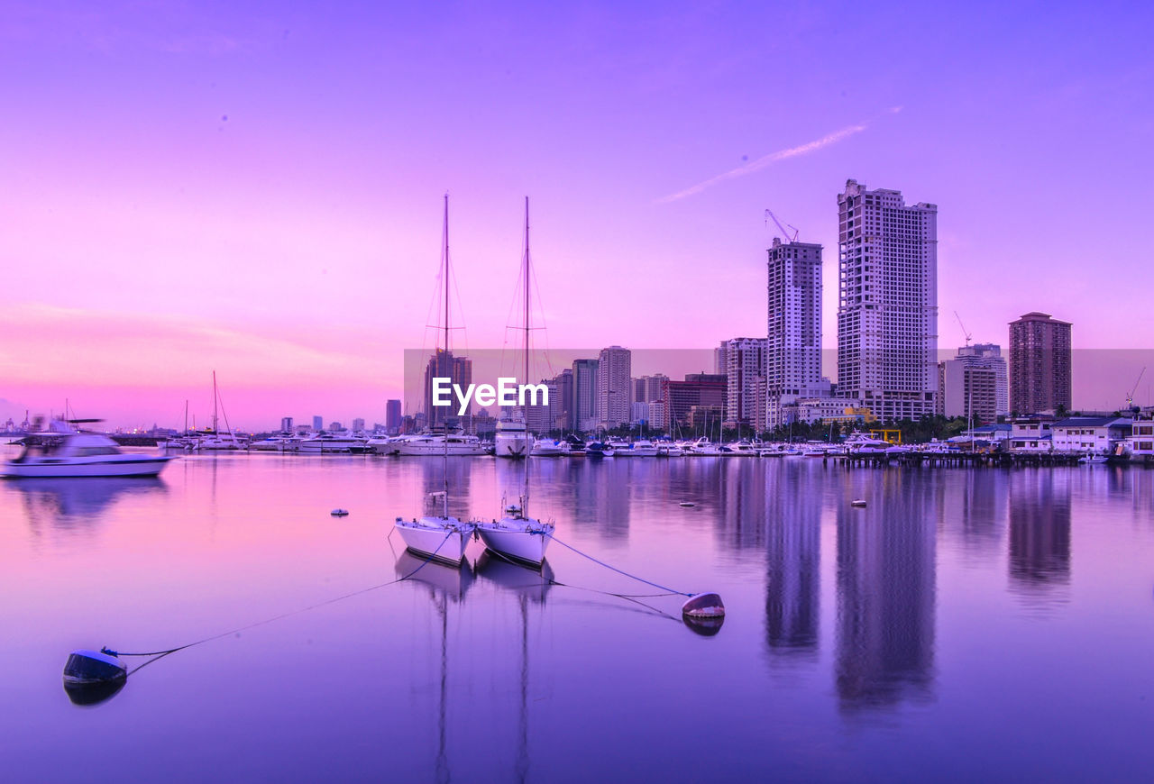 water, building exterior, architecture, sky, sunset, built structure, reflection, city, office building exterior, waterfront, building, skyscraper, transportation, nature, tall - high, no people, pink color, nautical vessel, modern, cityscape, purple, outdoors, spire, bay, sailboat