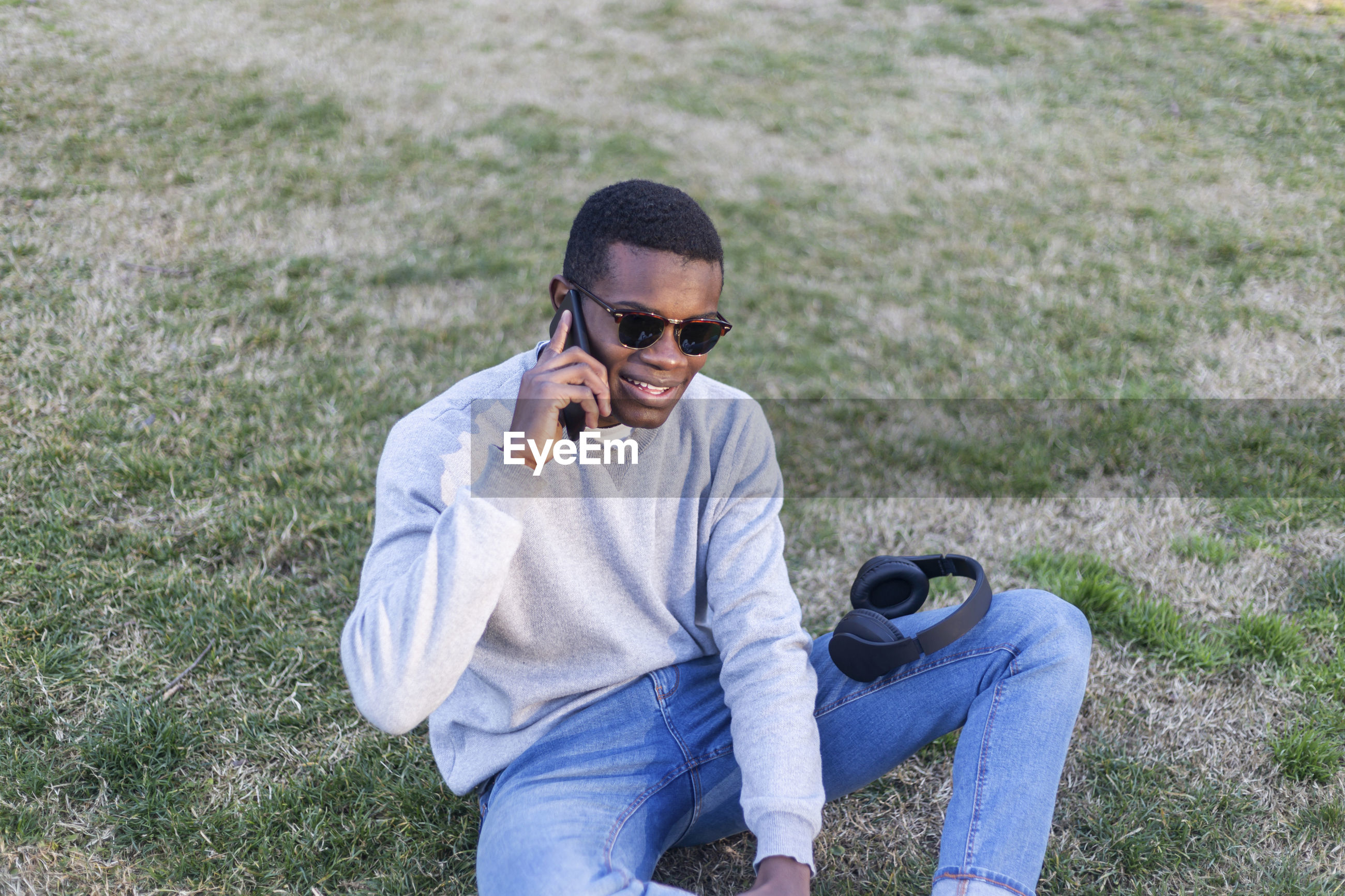 Smiling young man talking on phone while sitting at park