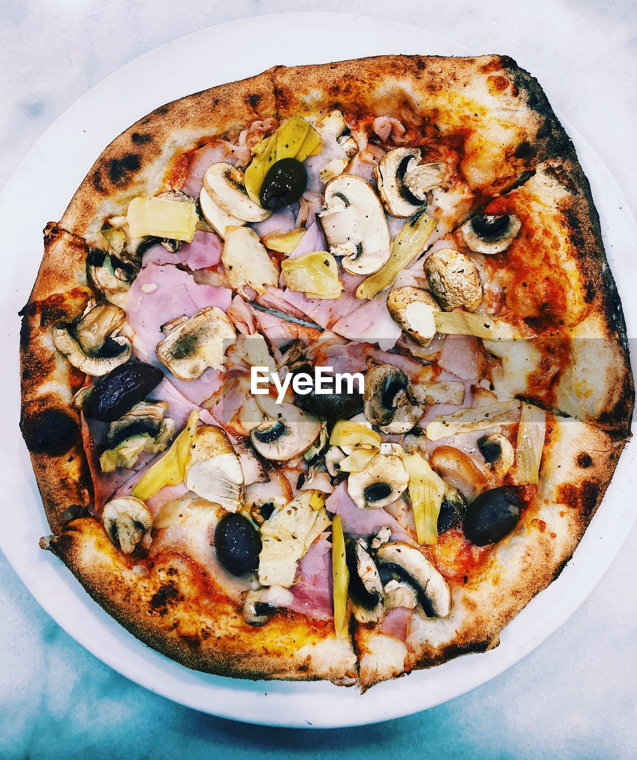 Directly above shot of pizza in plate on wooden table