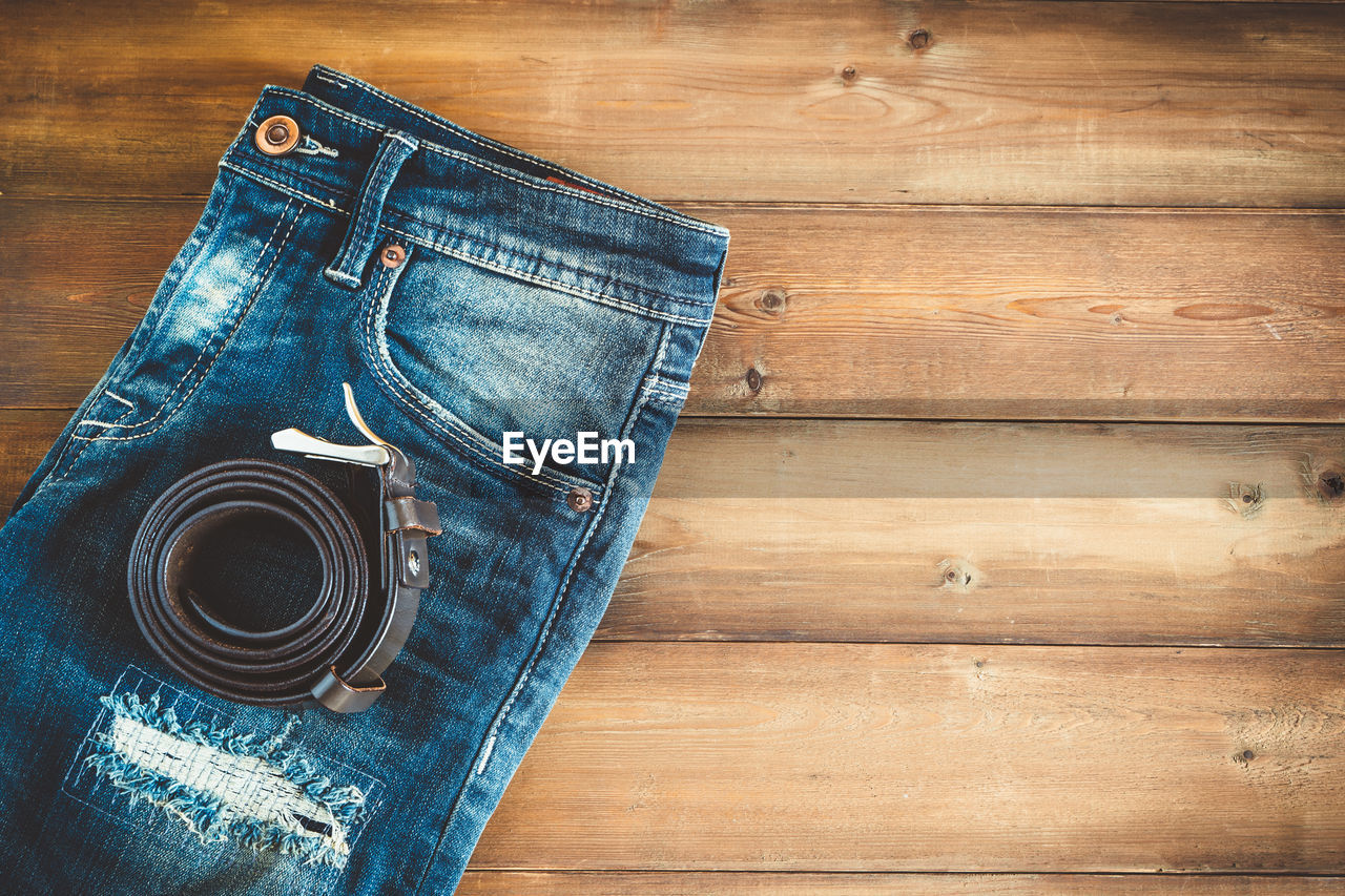 Directly above shot of belt and jeans on table