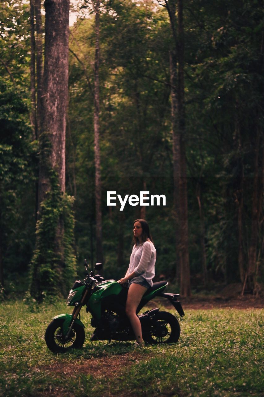Side View Of Woman Sitting On Motorcycle At Field In Forest