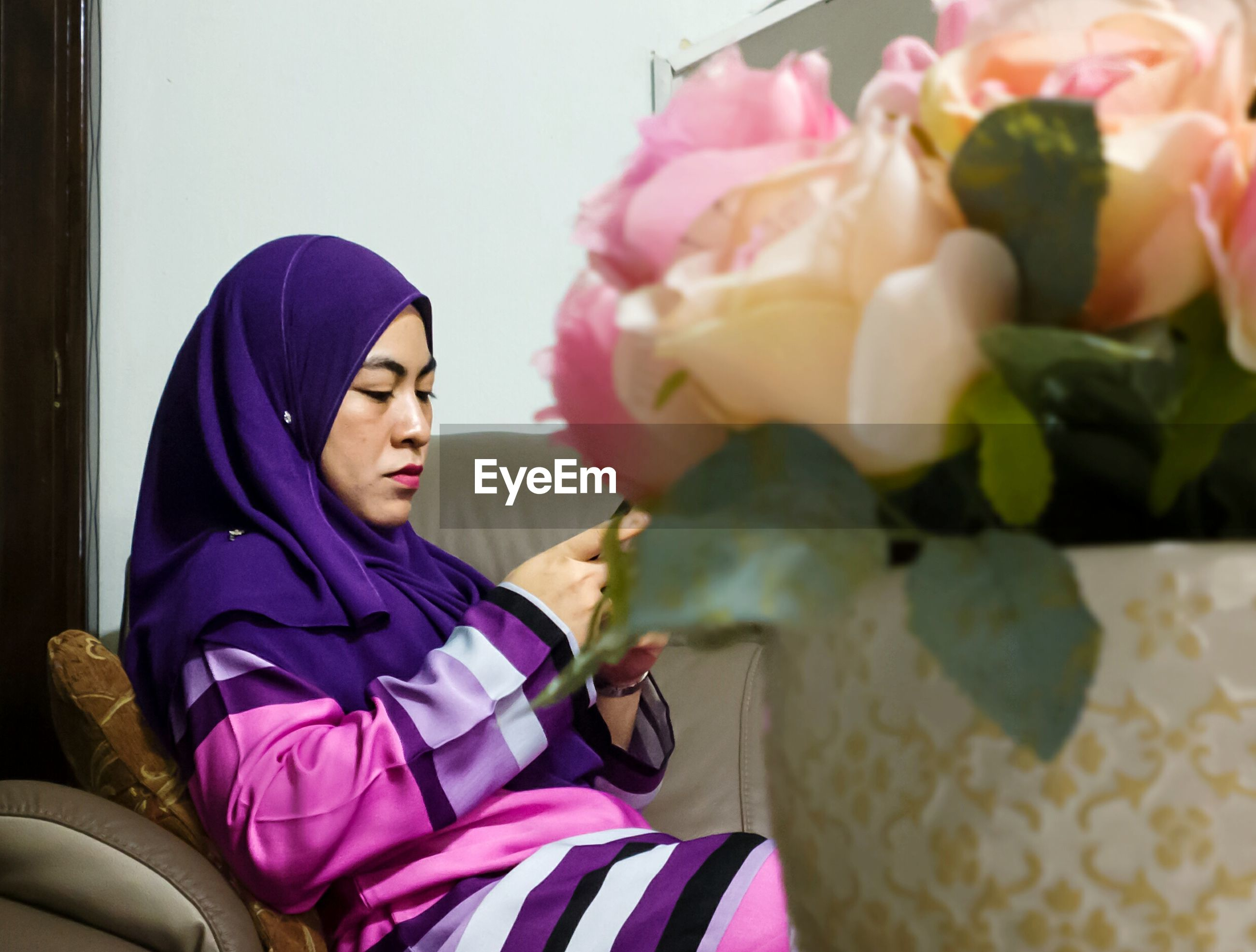 Woman wearing hijab while sitting at home