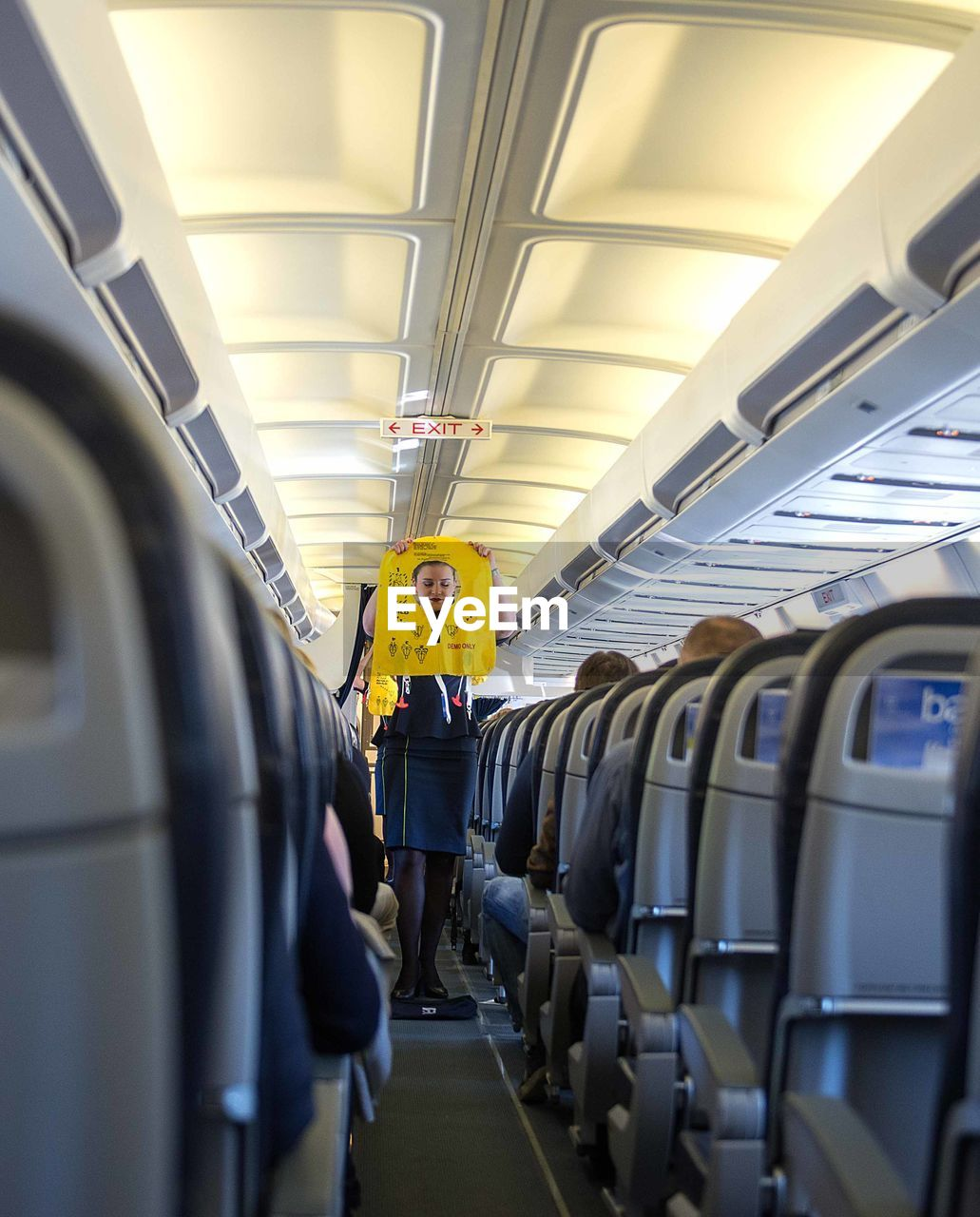 public transportation, vehicle seat, vehicle interior, mode of transportation, transportation, travel, seat, airplane, train, men, real people, indoors, air vehicle, rail transportation, train - vehicle, rear view, people, group of people, journey, incidental people, airplane seat, subway train, ceiling