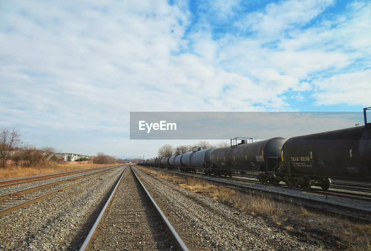 Diminishing Perspective Of Railroad Tracks Against Cloudy Sky