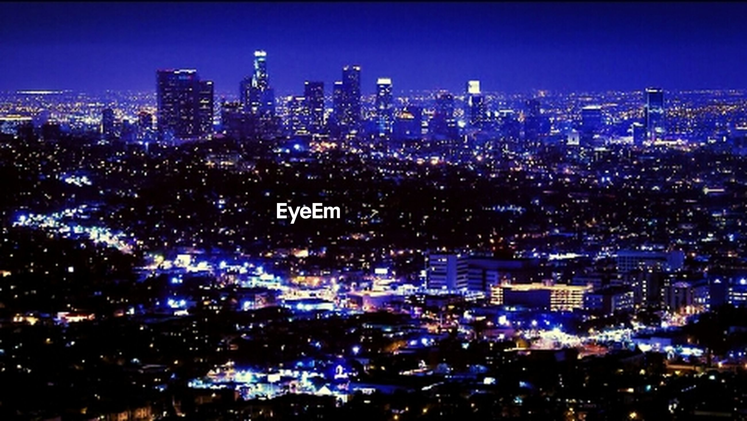 illuminated, city, building exterior, cityscape, night, architecture, built structure, skyscraper, crowded, high angle view, tall - high, urban skyline, tower, city life, modern, office building, residential district, clear sky, financial district, sky