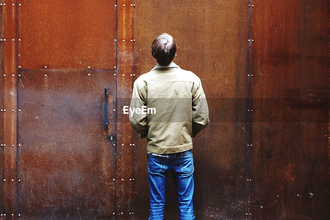 Rear view of man standing against rusty metallic wall