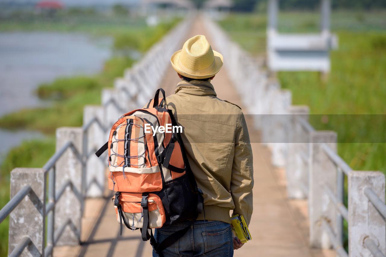 Hiker Walking On Pier Against Sky