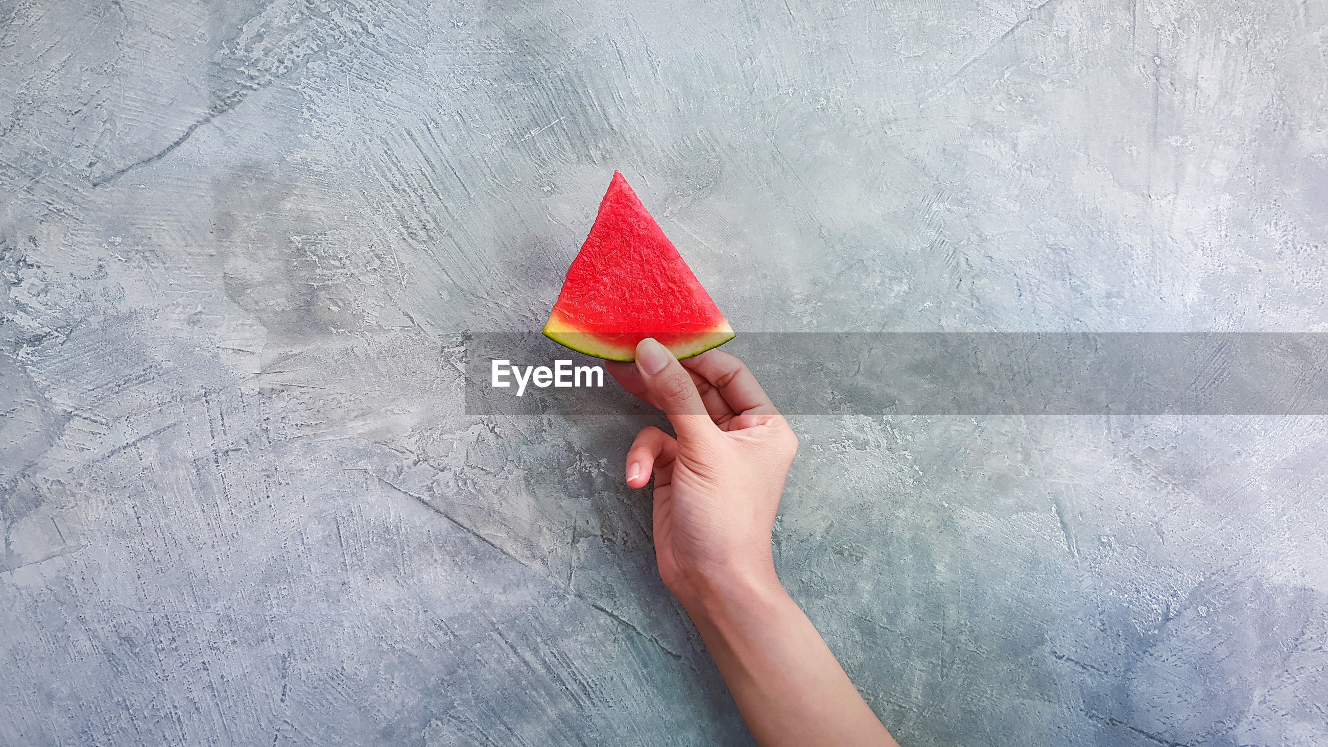 HIGH ANGLE VIEW OF HAND HOLDING RED FRUIT