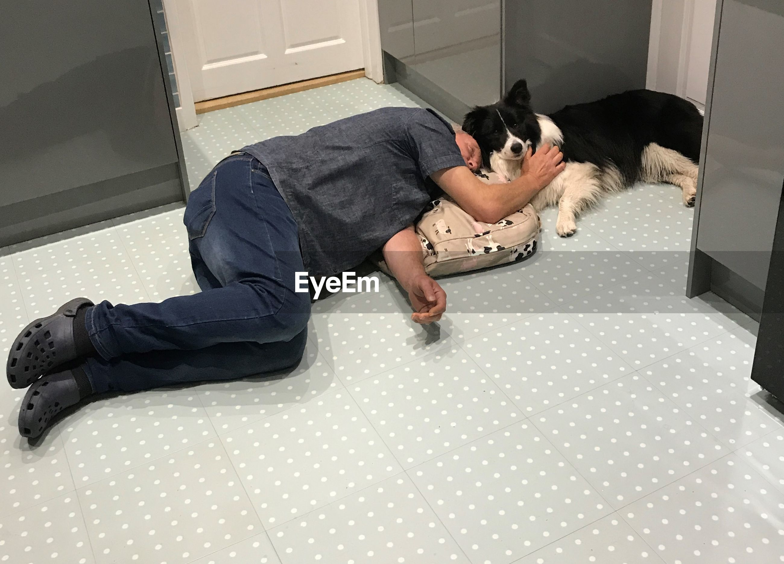 High angle view of man sleeping by dog on floor at home
