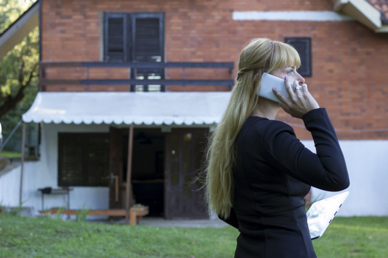 Businesswoman talking on mobile phone while holding digital tablet on outdoors