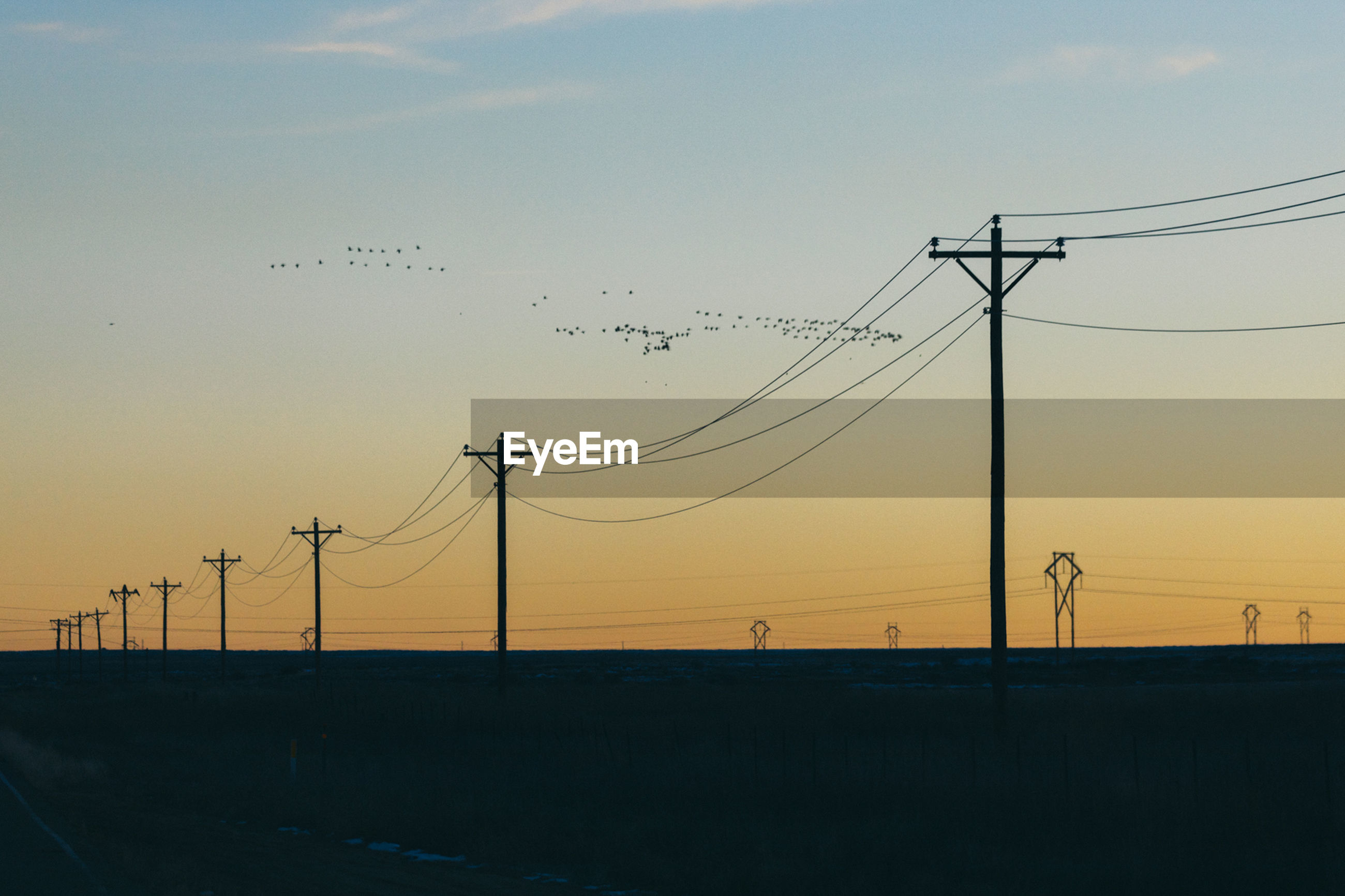 Silhouette electricity pylons against sky during sunset