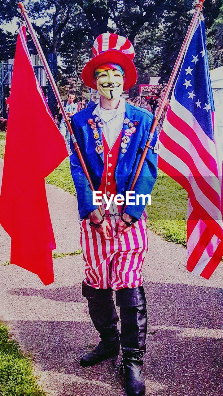 flag, red, outdoors, day, patriotism, one person, full length, looking at camera, real people, portrait, men, adults only, one man only, tree, only men, adult, people, young adult