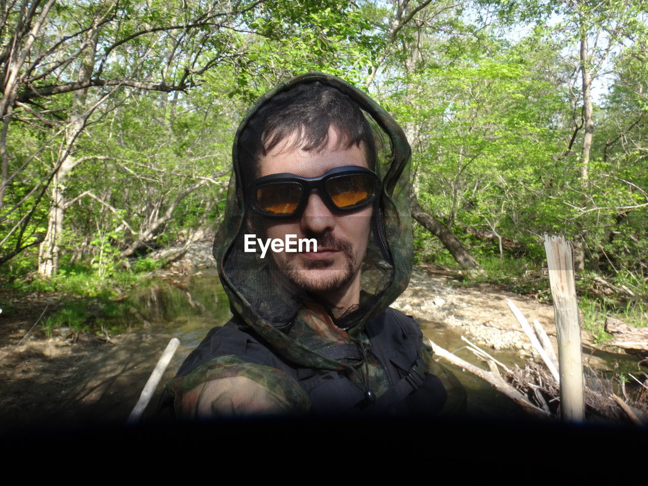 young adult, tree, headshot, sunglasses, portrait, one person, young men, outdoors, day, looking at camera, branch, forest, one young man only, nature, one man only, adult, adults only, only men, people