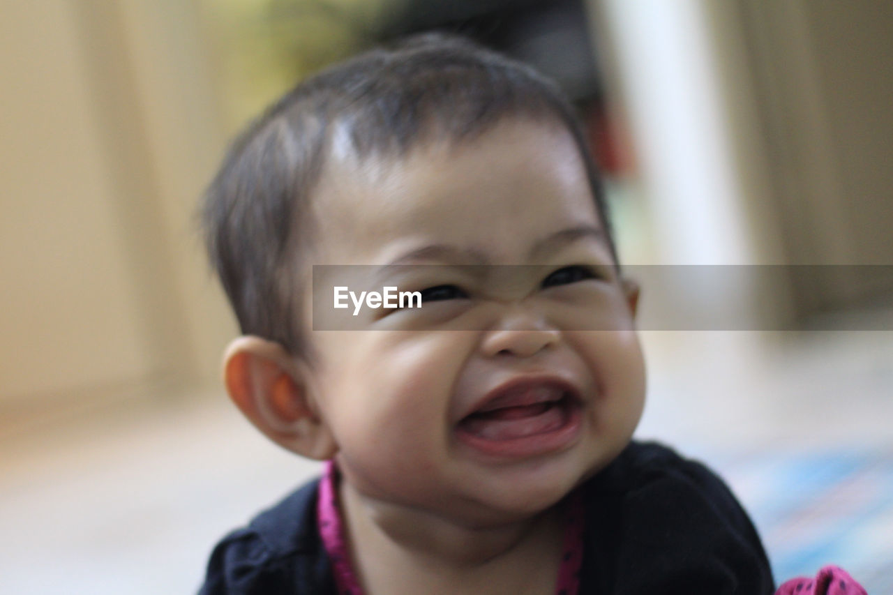 childhood, mouth open, baby, one person, innocence, human mouth, focus on foreground, real people, indoors, headshot, smiling, cute, close-up, happiness, laughing, human face, front view, cheerful, lifestyles, day, human body part, portrait, babies only, people