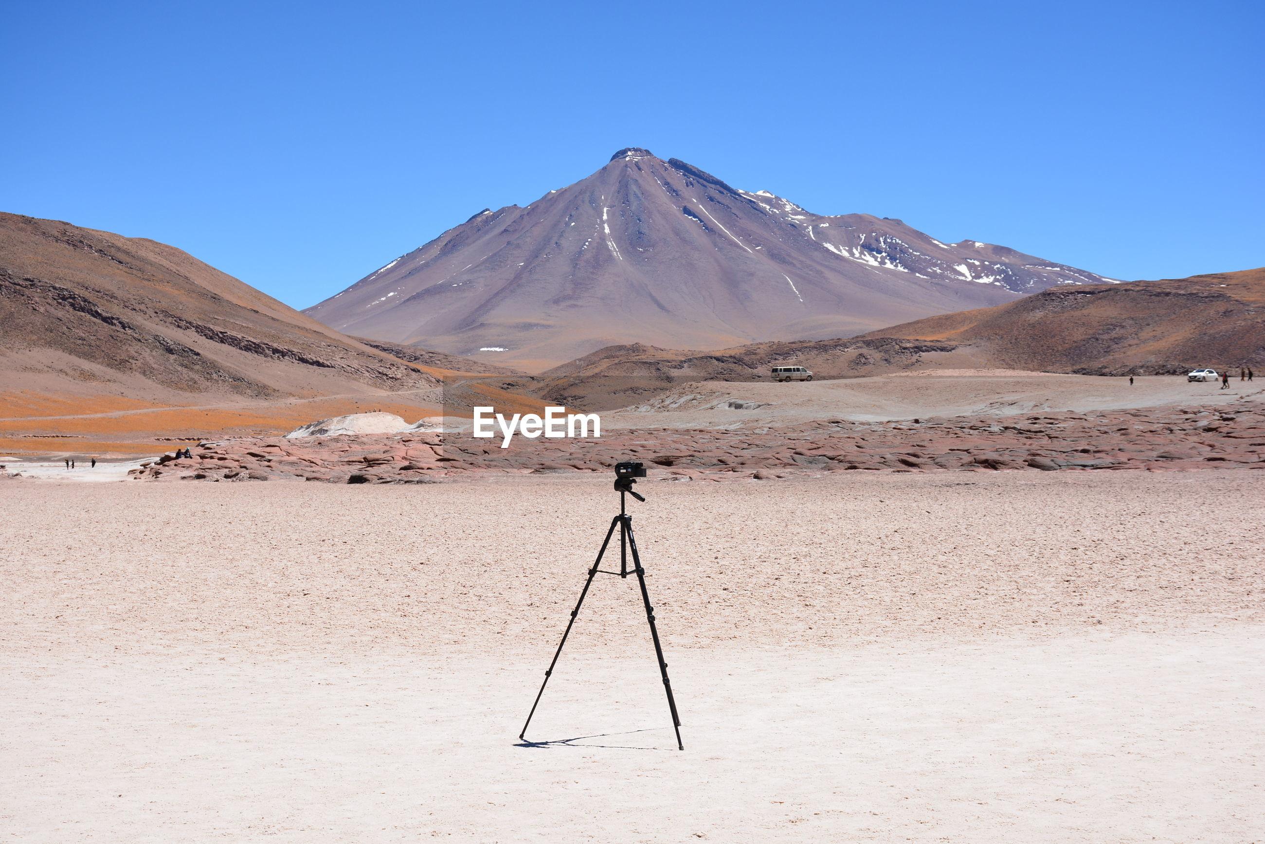 Tripod in desert against clear sky