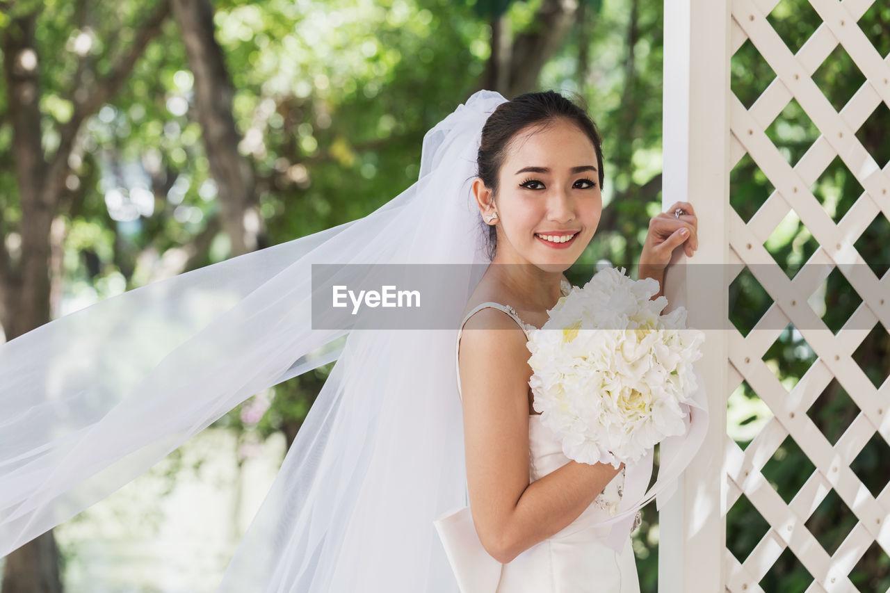 Portrait of smiling bride in wedding dress standing outdoors
