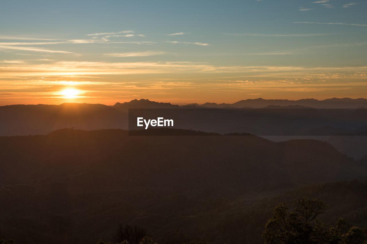 sunset, sky, beauty in nature, scenics - nature, tranquil scene, mountain, tranquility, orange color, idyllic, non-urban scene, silhouette, cloud - sky, no people, nature, mountain range, tree, sun, plant, environment, outdoors, hazy, mountain peak