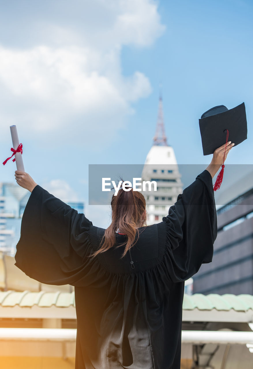 Woman In Graduation Gown Standing Against Sky