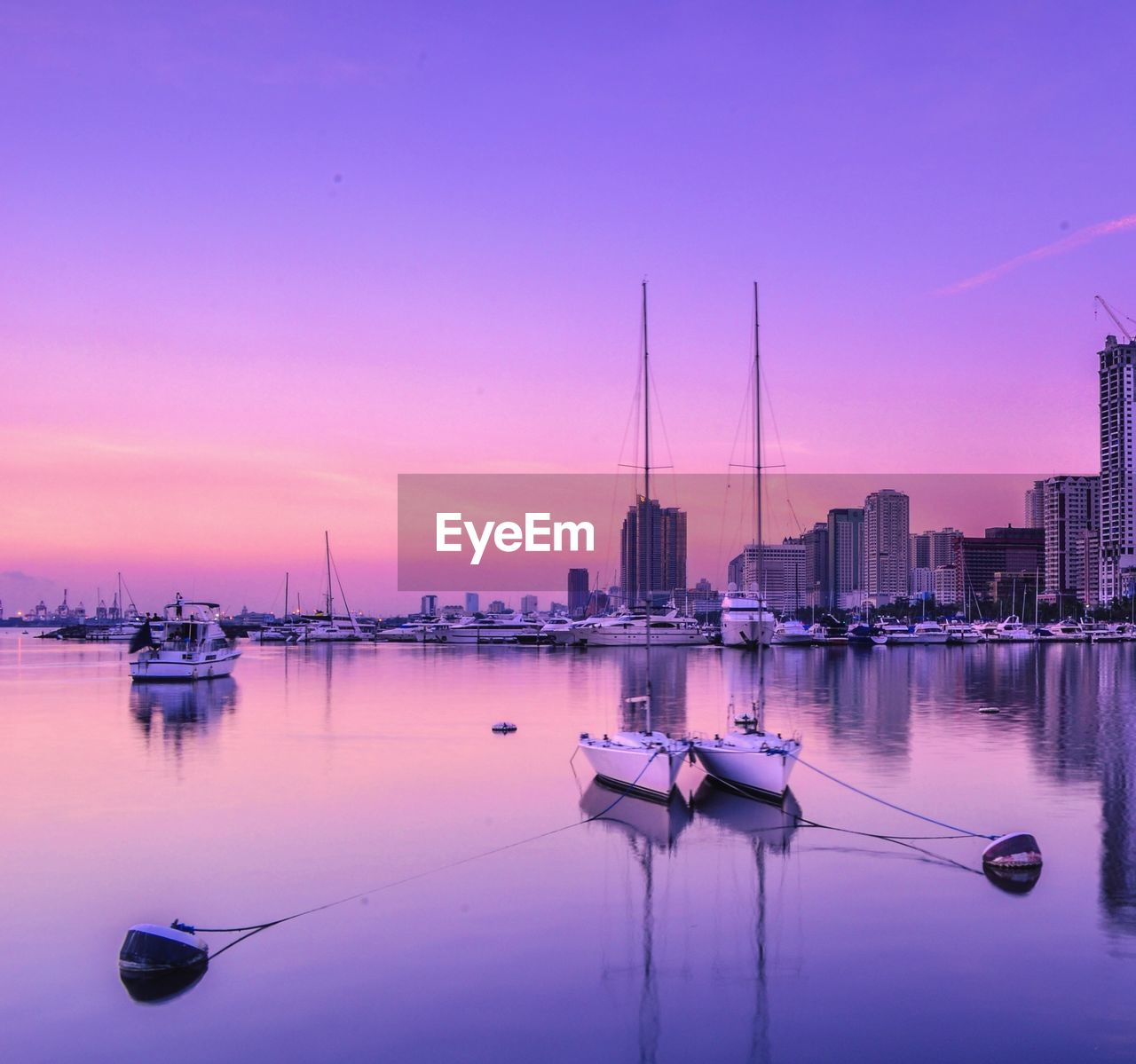 water, nautical vessel, sky, transportation, sunset, mode of transportation, reflection, architecture, building exterior, moored, built structure, waterfront, no people, city, nature, purple, tranquility, orange color, pink color, sailboat, outdoors, marina, office building exterior, skyscraper