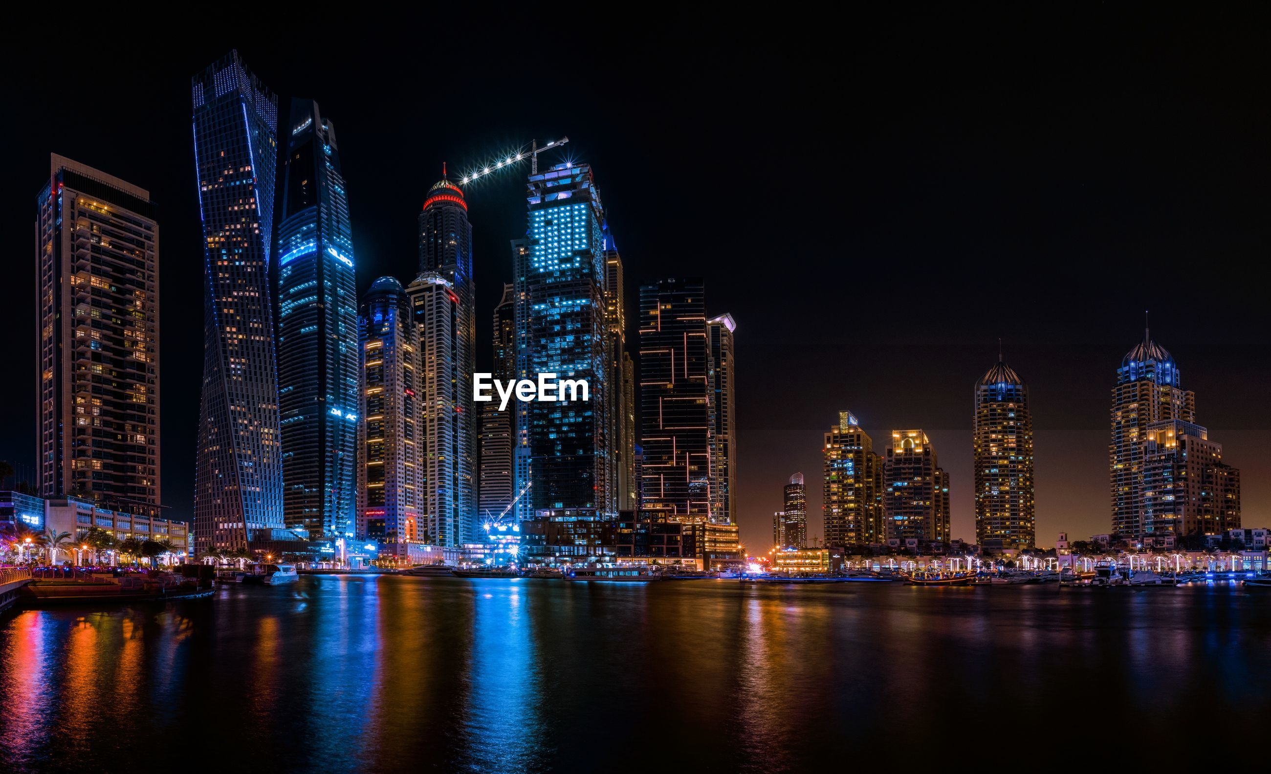 Illuminated modern buildings by river against sky at night