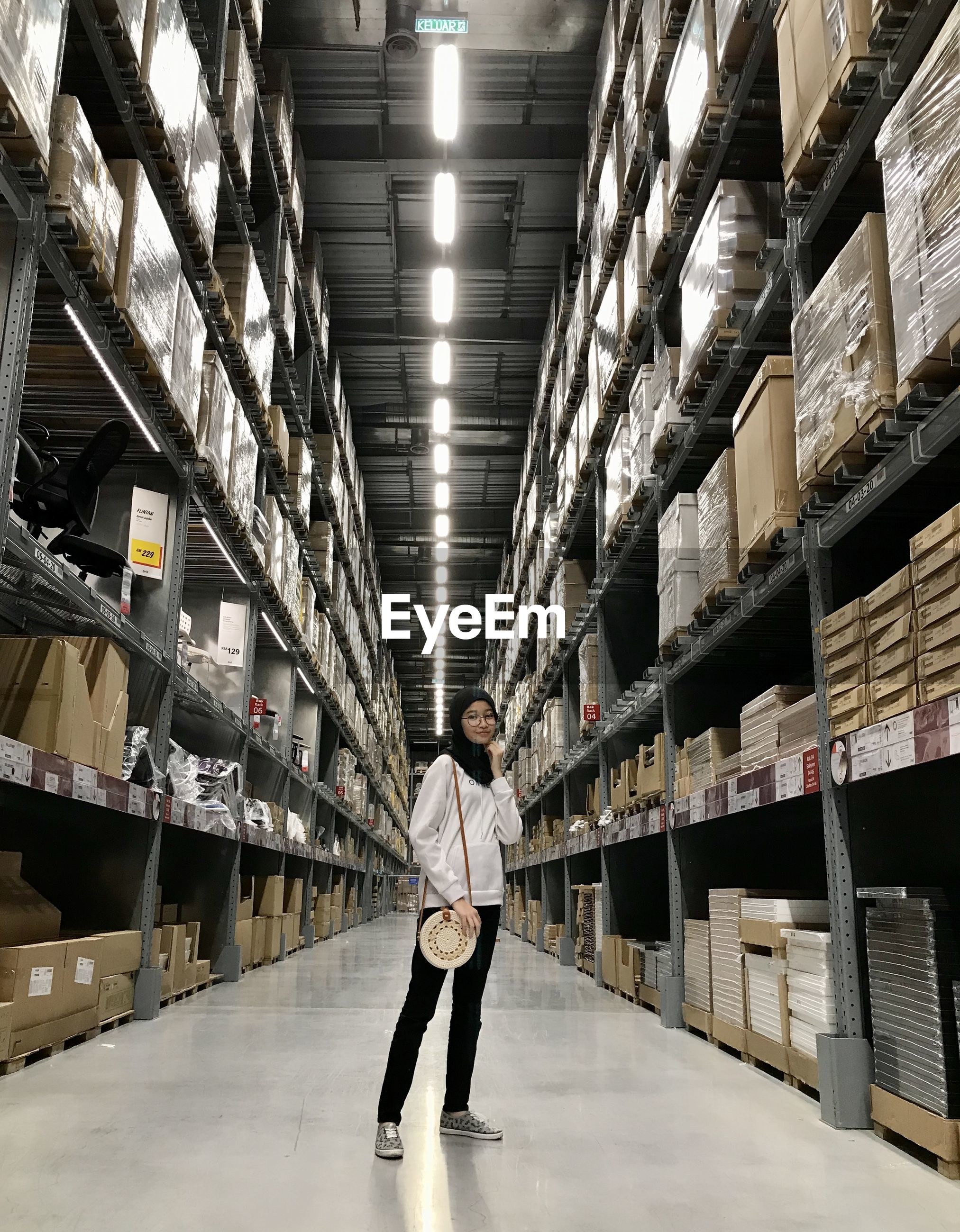 Full length of girl standing in warehouse